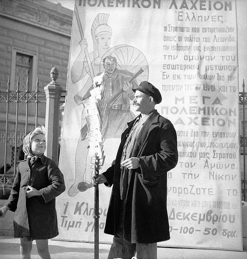 800px-Λαχειοπώλης_με_αφίσα_του_Μεγάλου_Πολεμικού_Λαχείου,_Νοέμβριος_1940