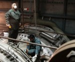 Public Power Corporation's employees repair a gas turbine compartment inside a power station at Lavrio town southeast of Athens