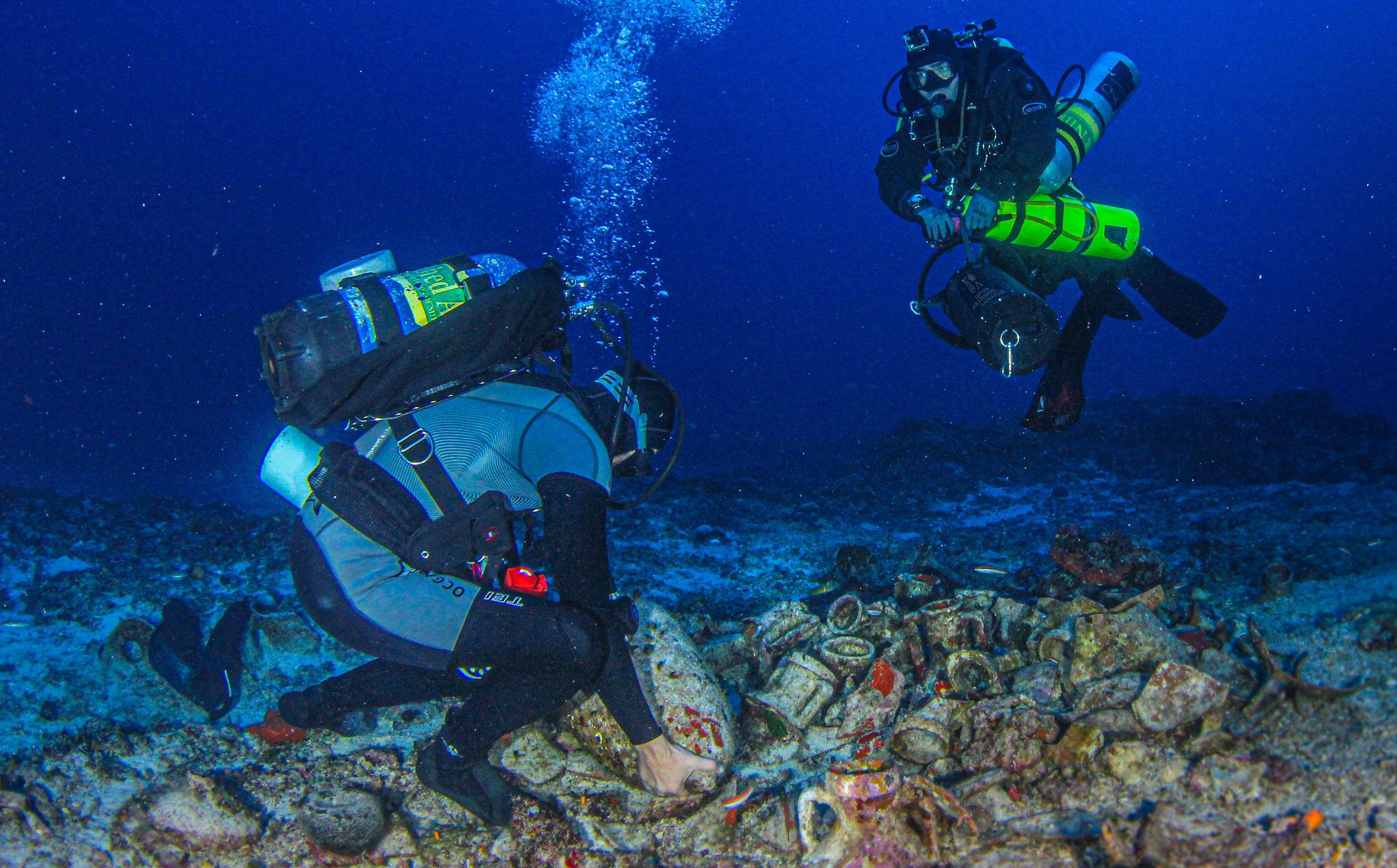 Ο επιστημονικά υπεύθυνος της έρευνας Δρ Γεώργιος Κουτσουφλάκης μετακινεί αμφορέα από το φορτίο του ναυαγίου των Αντικυθήρων. Παρακολουθεί ο τεχνικά υπεύθυνος Αλέξανδρος Σωτηρίου
