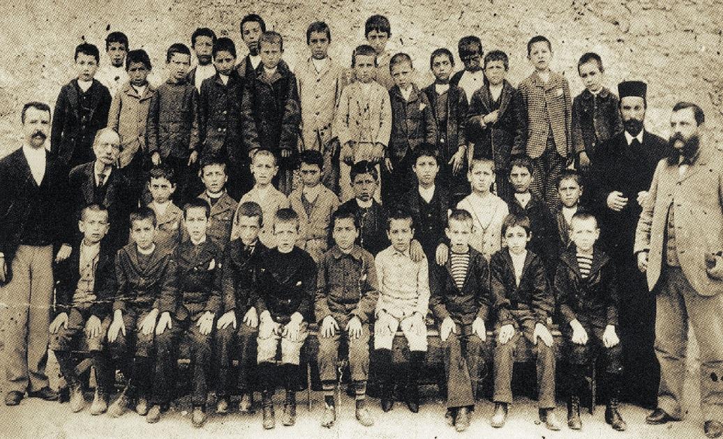 Φωτό 4: Δάσκαλοι και μαθητές Ελληνικού Σχολείου (τέλη 19ου αι.). Στην άκρη της φωτογραφίας ίσως είναι ο Θεοφάνης Κατωπόδης (παπά-Ατζουλής)