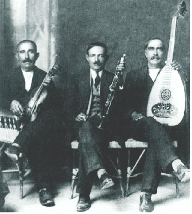 Ο σπουδαίος Πρεβεζάνος κλαριτζής Νίκος Τζάρας στην μέση, στα 1930, ο οποίος καλούνταν τακτικά σε Λευκαδίτικα πανηγύρια στην διάρκεια του μεσοπολέμου, ενώ δίδαξε σε αρκετούς Λευκαδίτες την τέχνη του κλαρίνου. Δεξιά του ο βιολιτζής Κώστας Μπενάτσης και αριστερά του ο λαουτιέρης Βασίλης Ντάλας. Η φωτογραφία είναι απ' την ιστοσελίδα της Βουλής των Ελλήνων.